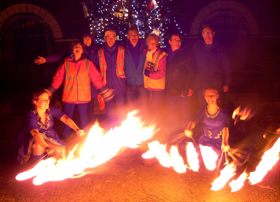 Members of Saintfield Development Association, who organised the Christmas Fair, pose at the end of the evening with fire performance group FirePoise.